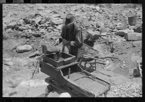 "Gold prospector pouring water through his ""rocker,"" Pinos Altos, New Mexico."